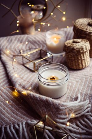 Burning hand-made candle with wooden wick in glass jar, cozy winter home decor