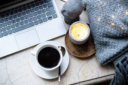 Cozy freelancers winter work place at home with cup of coffee
