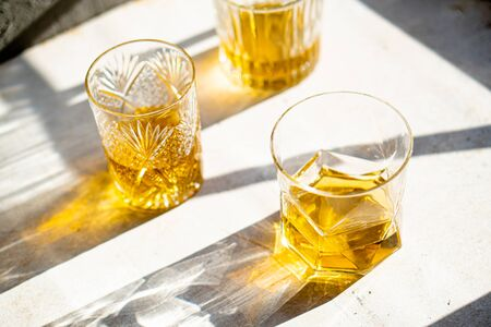 Whiskey in glasses on table in bright sunlight, yellow drink Imagens