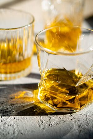 Whiskey in glasses on table in bright sunlight, yellow drink