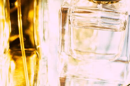 Beautiful bokeh and light reflections in yellow glass perfume bottles, abstract backgraound macro shot