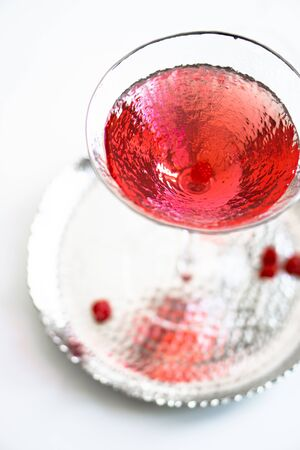 Classic red cocktail in crystal texture glass on white background, still life with drink