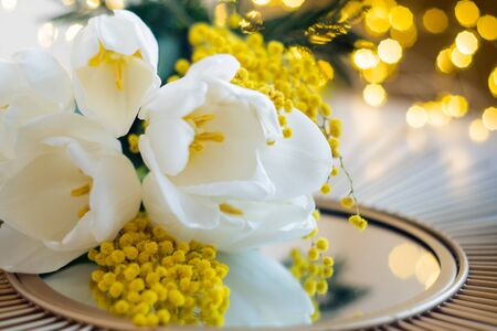Bouquet of white tulips and mimosa flowers on mirror tray, festive wedding floral decoration, artistic soft focus