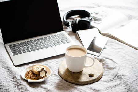 Real home workplace, laptop with cup of coffee with cookies on bed with cozy blanket, freelancers workplace Stockfoto