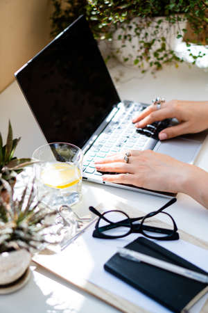 Woman's hands on laptop keyboard, cozy workplace