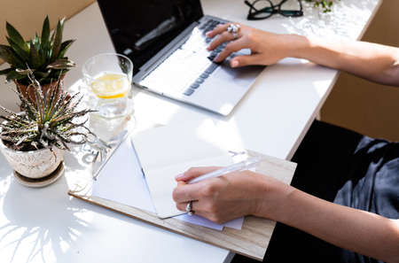 Womans hands on laptop keyboard, writing in notepad