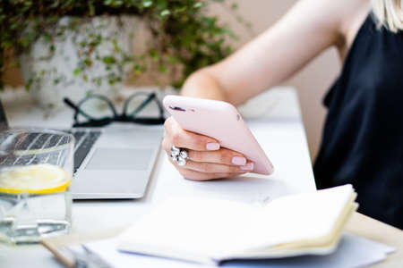 Womans hand holding smartphone in cozy summer office with laptop and green plants Stock fotó