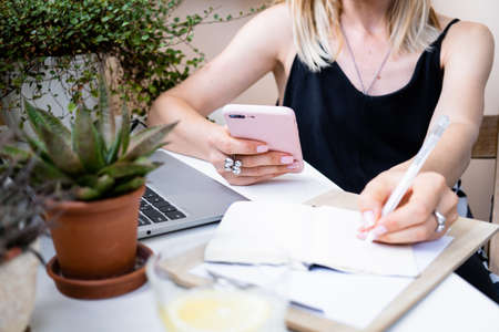 Womans hand holding smartphone and making notes in notepad in cozy summer office with laptop Stock fotó