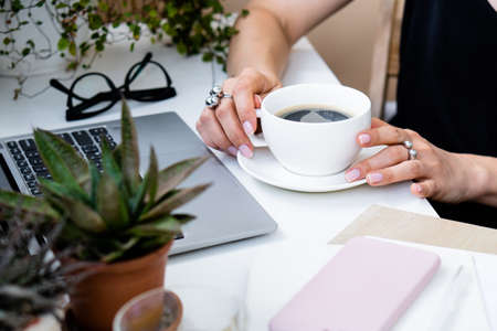Womans hand holding cup of coffee in cozy summer office with laptop and green plants
