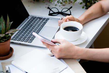 Womans hand holding cup of coffee and smartphone in cozy office with laptop and green plants