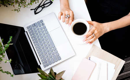 Womans hands holding cup of coffee in cozy office with laptop and green plants Stock fotó