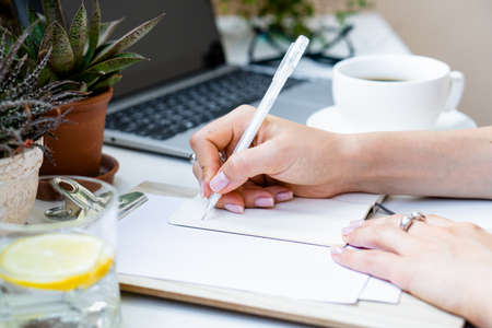 Womans hands making notes in notepad in cozy summer office with laptop and green home plants
