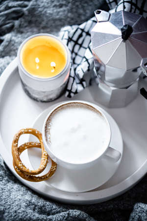 Cup of coffee on tray in cozy winter bad with wool blanket
