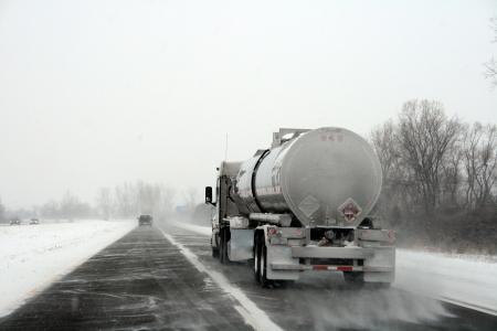 windswept: Tanker Truck in Windswept Snow Storm Stock Photo