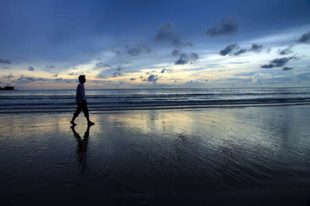 In a sunset scene, a man walks along Nai-yang beach Phuket  take on Sept 2010 photo
