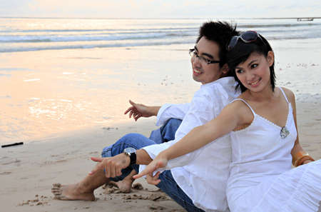 In a sunset scene, man and woman sit on the beach photo