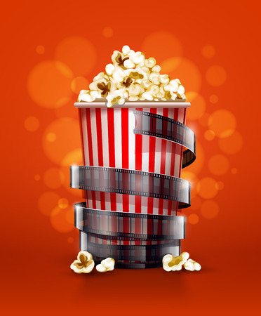 cinema concept with paper bucket with popcorn and movie film tape.