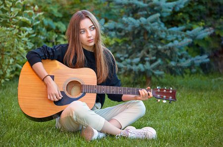 Guitarist girl play music on guitar. Beautiful teenager singer, musician with long hair and musical instrument in hands sitting on the green grass in the city park.