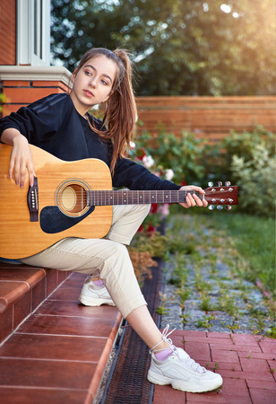 Guitarist girl play music on the guitar. Beautiful teenager singer, cool musician with long hair and musical instrument in hands sitting on the stairs. Stockfoto