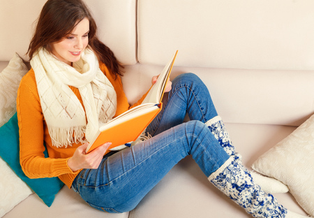 Girl reads a book lying at white soft sofa, culture lifestyle, leisure. Young woman reading art literature Stockfoto