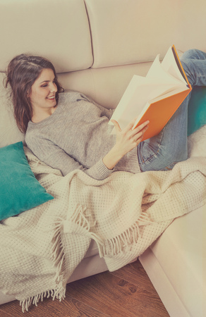 Girl reads a book lying at white soft sofa, culture lifestyle, leisure. Young woman reading art literature. Stockfoto