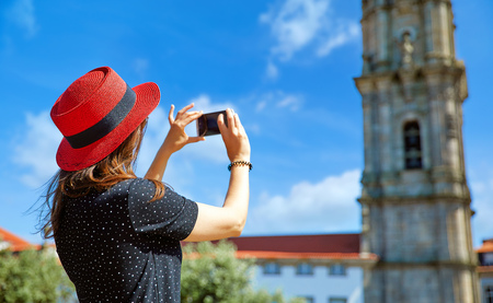 Young girl in red hat with smartphone in hands take photos of ancient tower during travel in Lisbon, Portugal. Stockfoto