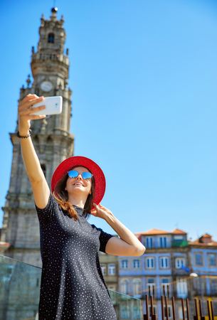 Young beautiful girl in red hat take selfie with phone on background of ancient tower and old houses during travel in Lisbon, Portugal.