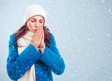 Frozen girl in blue coat, white hat and scarf heats hands among winter snowstorm Stockfoto