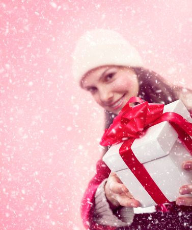 Young girl in snow gives a christmas gift with red bow and ribbon