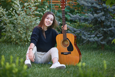 Guitarist girl with guitar. Beautiful teenager singer, musician with long hair and musical instrument in hands sitting on the green grass in the park.