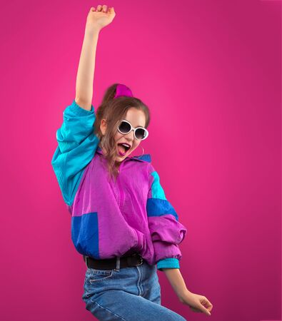 Fashion DJ girl in colorful trendy jacket enjoys dancing music 90s. Teenager Girl in vintage retro sunglasses dances at the disco party of 80s vibes. Fashionable young model on purple color background.