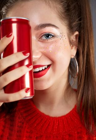 Portrait of beautiful smiling teenager girl in casual hipster clothes with stylish trendy makeup white drinking cool soda cola drink from red can in hand. Smiling face with beautifil eyes and red lips. Banque d'images