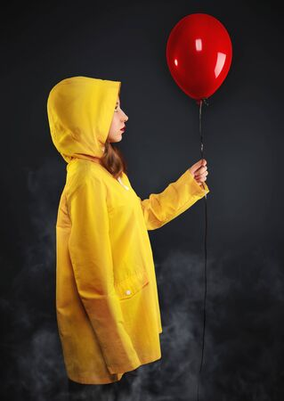 Sad little girl in haze in yellow coat with hood hold red air balloon in hand. Studio portrait on dark background with white smoke. Childhood fears and terror concept.