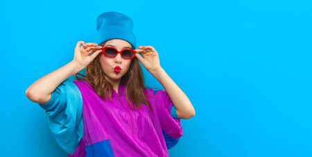 Cool teenager. Fashionable DJ girl in colorful trendy jacket and vintage retro sunglasses enjoys style of 80s — 90s vibes. Teenager Girl at disco party. Young fashion model on blue color background. Banque d'images