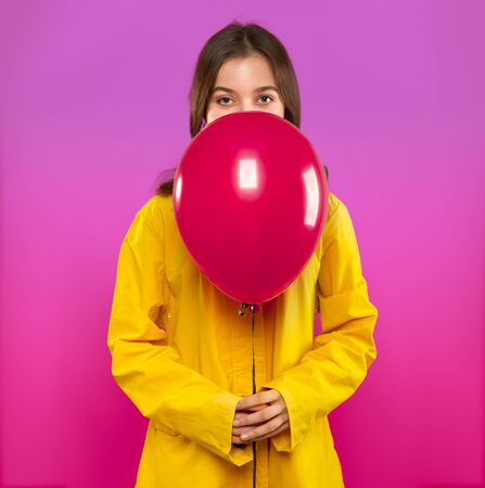 Pretty girl teenager in yellow coat with pink air balloon in hands on modern trendy violet background. Concept to Valentines day holiday. Studio portrait.