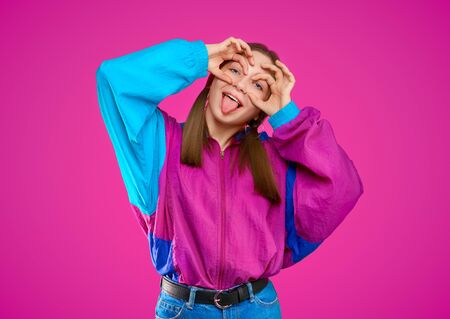 Fashion DJ girl in colorful trendy jacket from 90s. Teenager Girl shows funny face with tongue at the disco party of 80s vibes. Fashionable young model on purple color background. Banque d'images