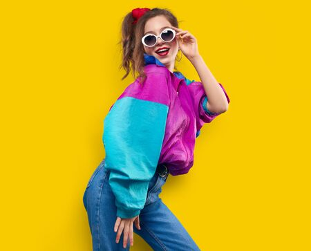 Cool teenager. Fashionable DJ girl in colorful trendy jacket and vintage retro sunglasses enjoys style of 80s — 90s vibes. Teenager Girl at disco party. Young fashion model on yellow color background.