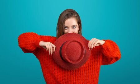 Red hat. Young stylish teenager girl in red sweater. Hat in hands. Fashionable, pretty cool model with long hair on blue background. Studio portrait.