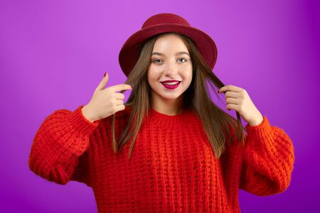 Red Hat. Young smiling stylish teenager girl in red sweater and vintage hat. Fashionable, pretty cool model with long hair on violet background. Studio portrait.