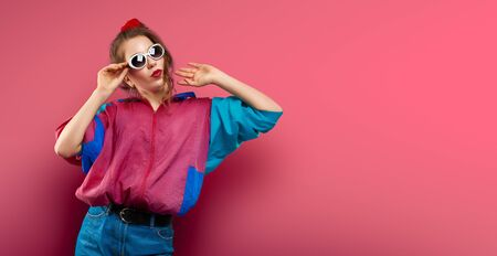 Cool teenager. Fashionable DJ girl in colorful trendy jacket and vintage retro sunglasses enjoys style of 80s - 90s vibes. Teenager Girl at disco party. Young fashion model on coral red background. Banque d'images