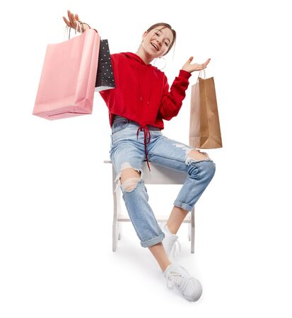 Young beautiful smiling girl in red sweetshot and blue jeans with paper bags for shopping sitting on chair after buying. Shopping concept, isolated on white background.