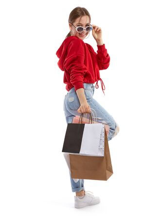Young beautiful smiling girl in red sweetshot, trendy sunglasses and blue jeans with paper bags for shopping posing happy after buying. Shopping concept, isolated on white background. Banque d'images