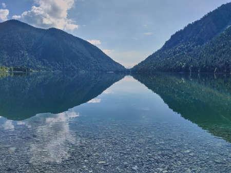 Mountain landscape reflects in glassy lake. Reflections in mountain lake. 免版税图像