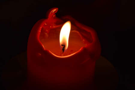 Red christmas candle on black background.