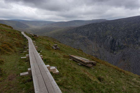 Wooden path leading through the Wicklow Mountains, Ireland. Wooden path in foggy mountain landscape.