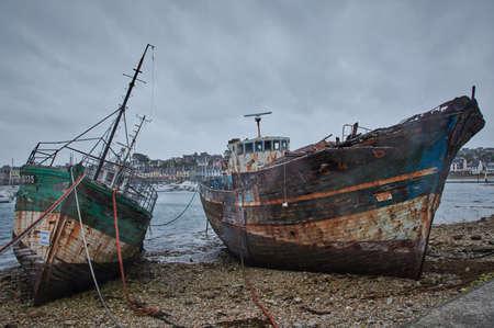 Old shipwrecks stranded in a harbor in Brittany, France.