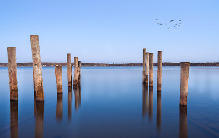 Mooring posts leading in turquoise blue sea  Aland island Finland
