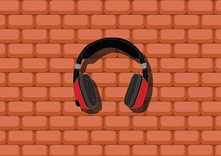 Red-black headphones hangs in front of the brick wall.