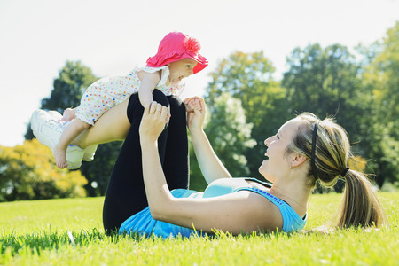 babies playing outside: A mother training with baby on a summer day Stock Photo
