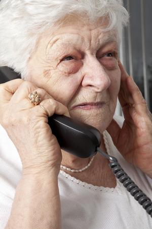 peinzende bejaarde vrouw die op de telefoon